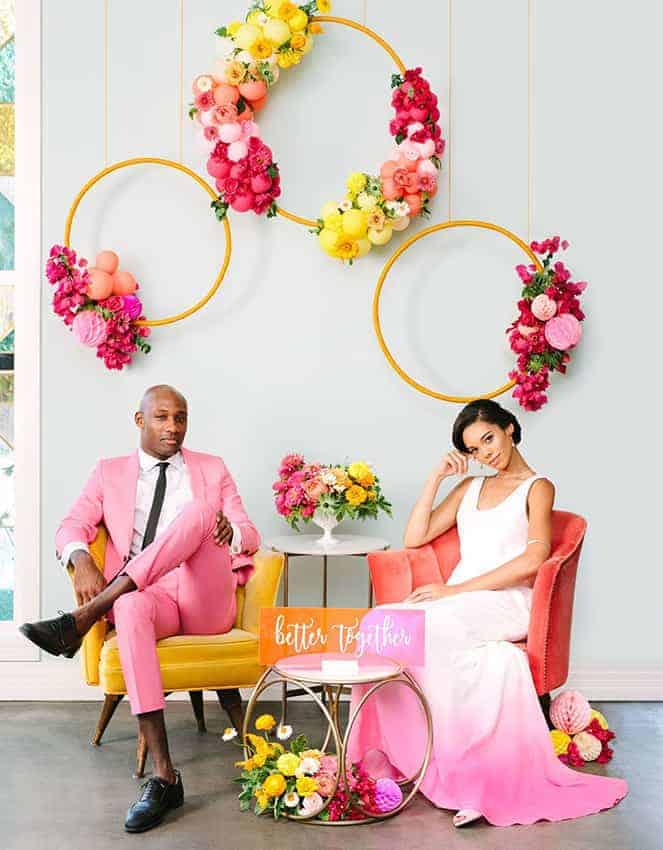 groom with pink suit and the bride with a white pink wedding dress, wedding colour decoration with hanging circles with colourful balloons and flowers