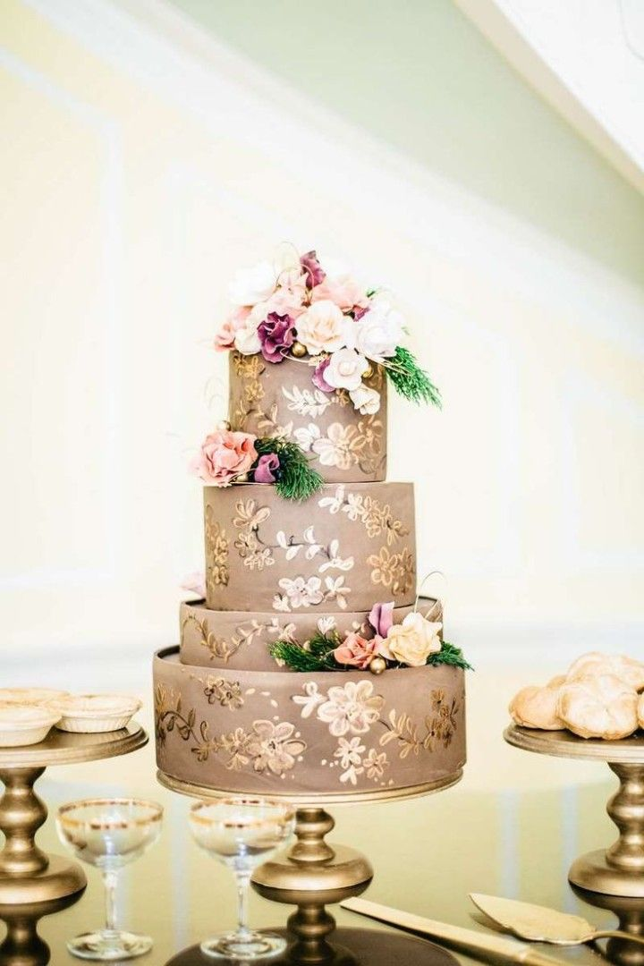 golden painted wedding cake with flowers on top