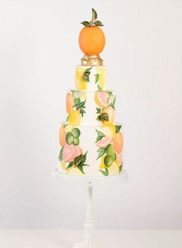 γαμήλια τούρτα με ζωγραφισμένα φρούτα και στην κορυφή ένα πορτοκάλι