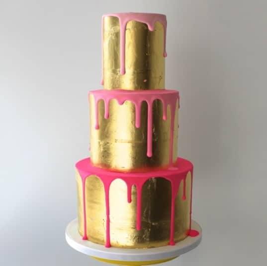 golden wedding cake with pink details