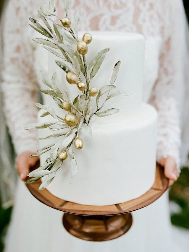 white wedding cake with olive leaves and golden details