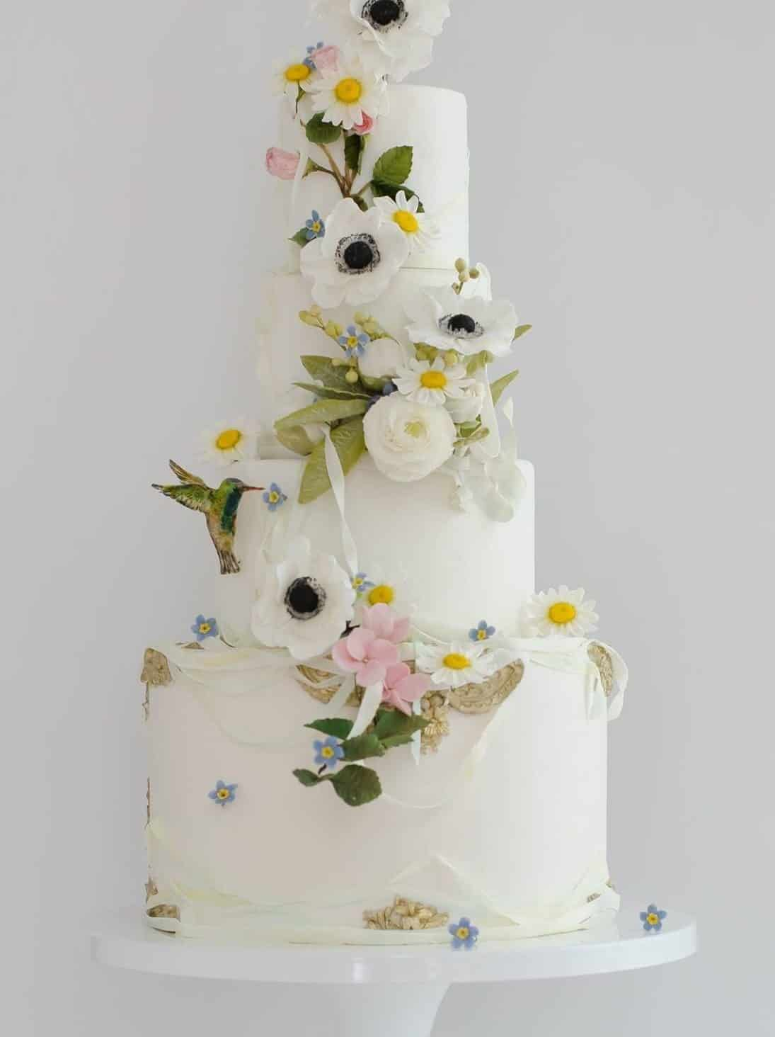 wedding cake with with anemone and daisies