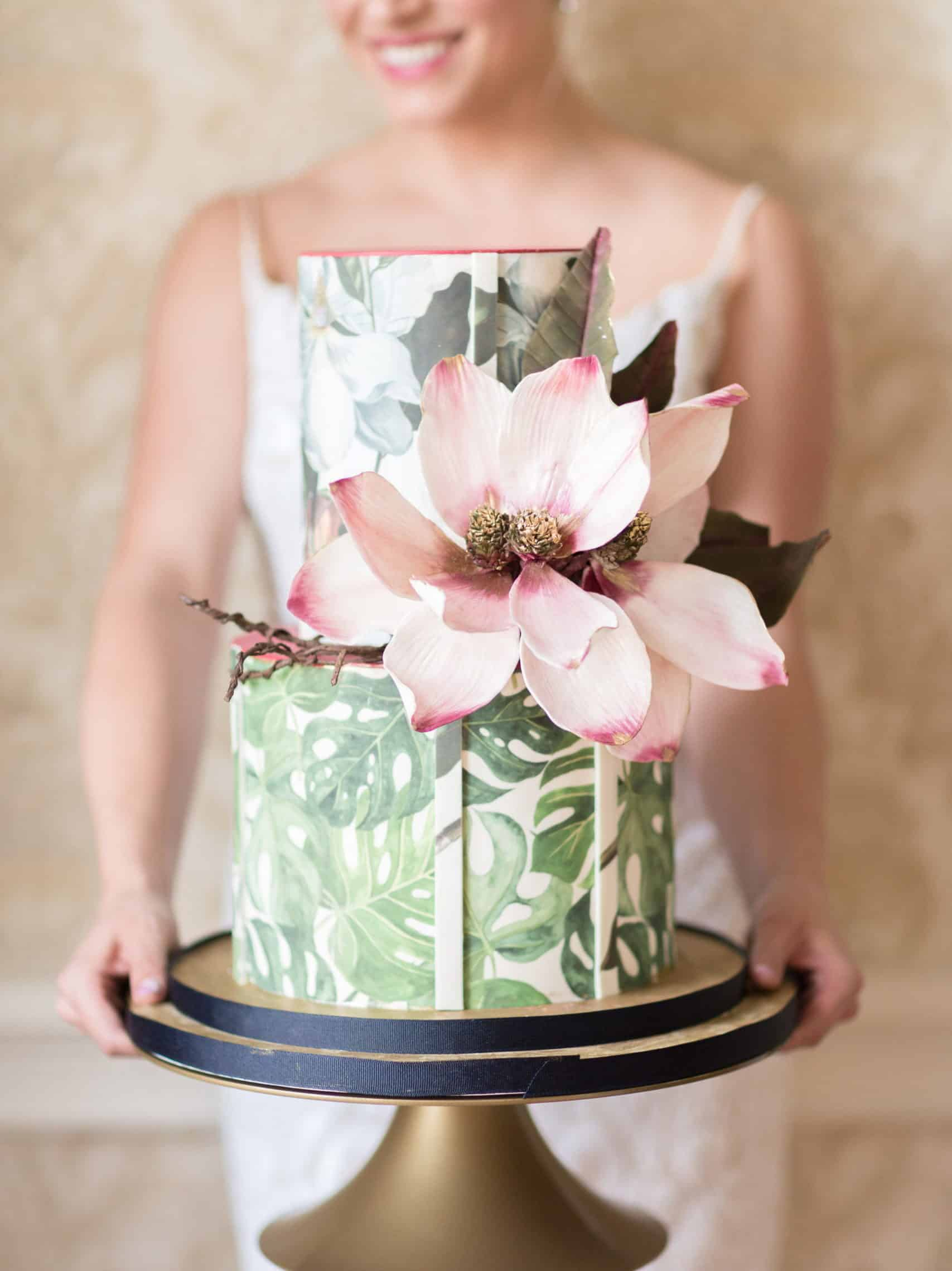 wedding cake with tropical painted leaves and pink flower