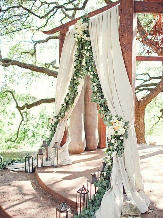 backdrop decoration with white curtains decorated with roses and greenery