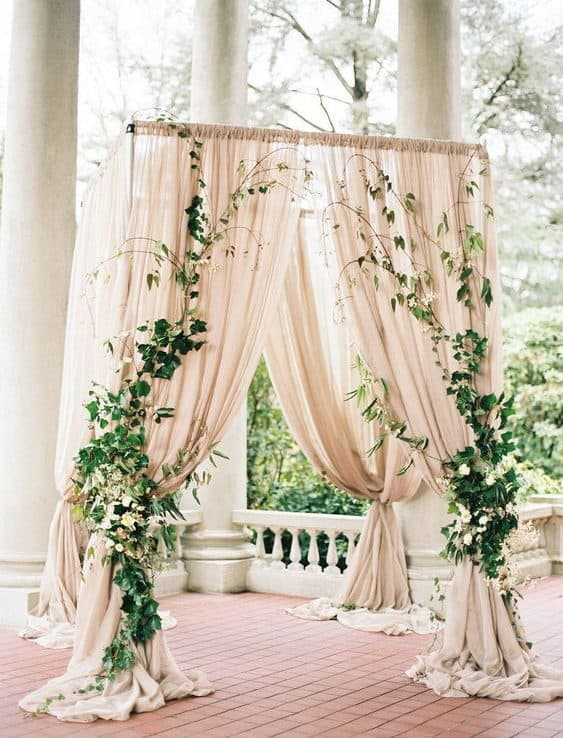 backdrop decoration with airy pink fabrics, placed like curtains and decorated with flowers