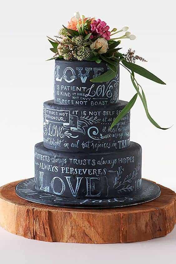 γαμήλια τούρτα σε μαύρο χρώμα με λουλούδια στη κορυφή