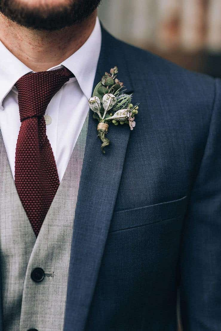 γαμπρός με μπλε κοστούμι . μπουτονιέρα με αγριολούλουδα και μπορτό γραβάτα
