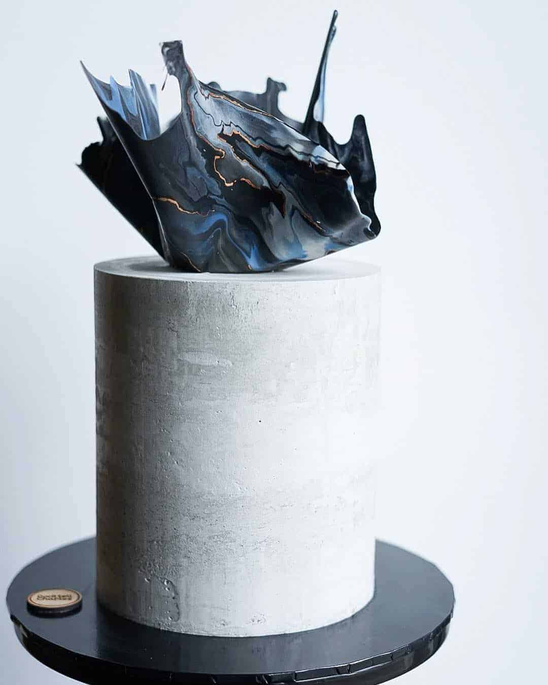 wedding cake with concrete texture and blue cake topper