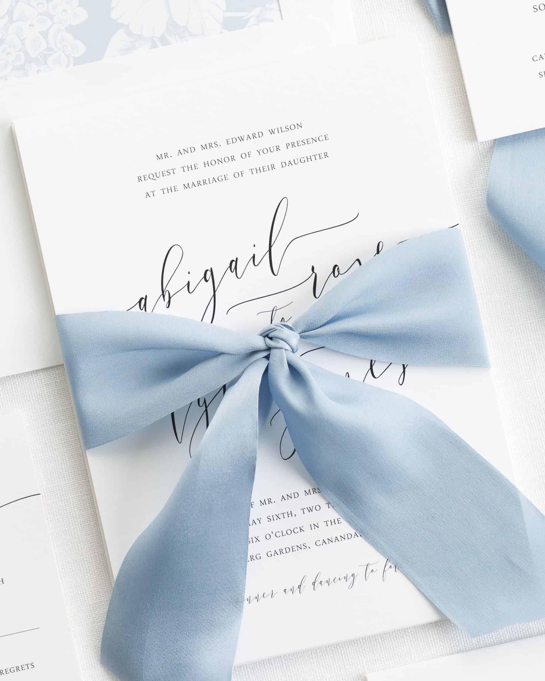 wedding invitation with a dusty blue ribbon