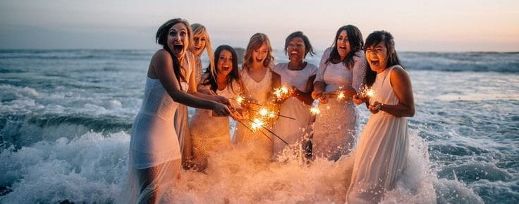 bride and her friends hop into the sea and turn on the fireworks