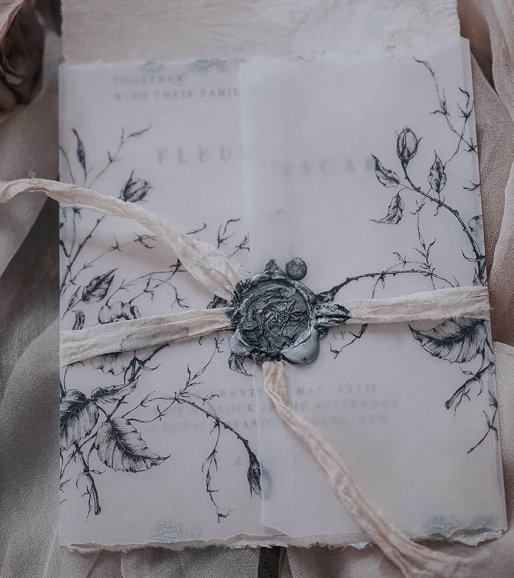 γαμήλια προσκληση με ανακυκλώσιμο χαρτί σε φάκελο από ριζόχαρτο και βουλοκέρι σε γκρίζο χρώμα και λεπτομέριες από τριαντάφυλλο