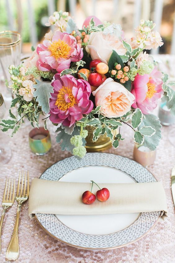 wedding decoration centrepiece with flowers and cherries and a cherry on the plate