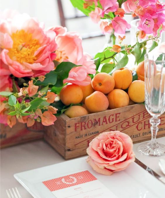 wedding decoration centrepiece with a wooden box of peaches and pink roses