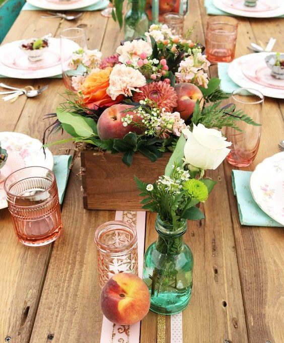 wedding decoration centrepiece with a wooden box with flowers and dark peaches