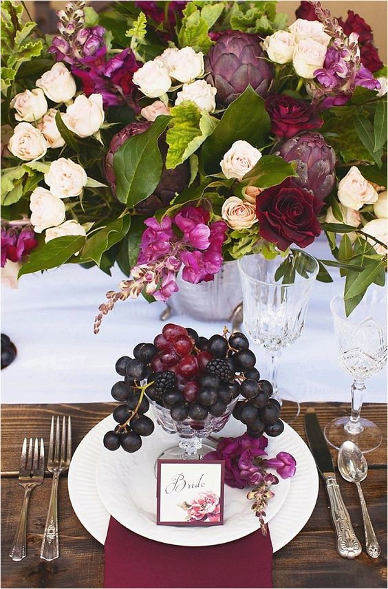 wedding decoration centrepiece with overflowing with flowers and cocktail made of forest fruit on the plate