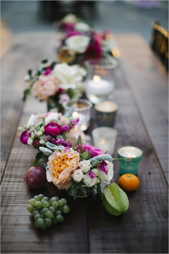 wedding decoration centrepiece with tealights candles fruit and handmade jars with freshly cut flowers