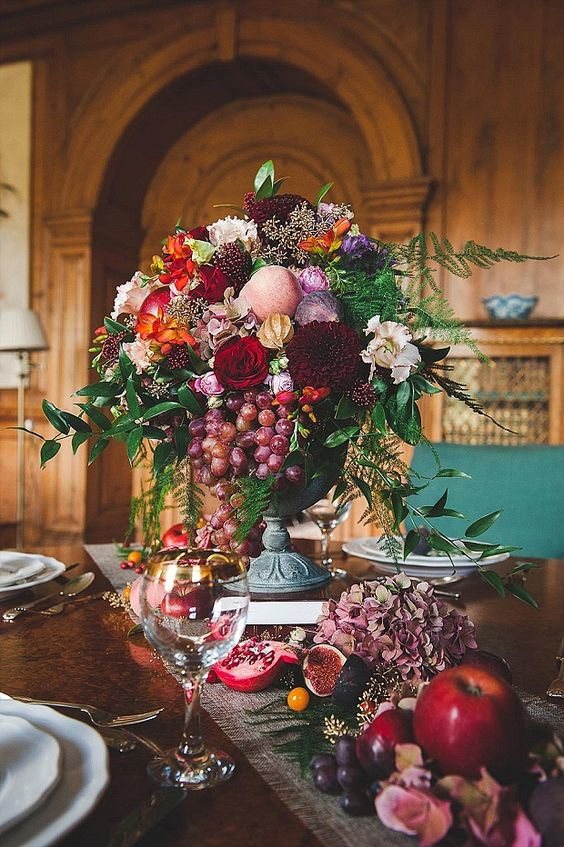 wedding decoration centrepiece with a composed with flowers and fruits, pomegranate, grape and apple
