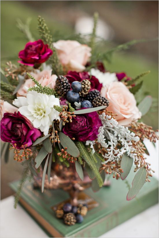 wedding decoration centrepiece with blueberries and blackberries and roses in shades of purple, fuchsia, white and soft pink