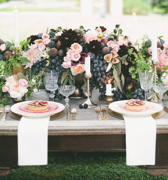 wedding decoration centrepiece with black grapes and figs, burgundy and pink flowers and bronze vases