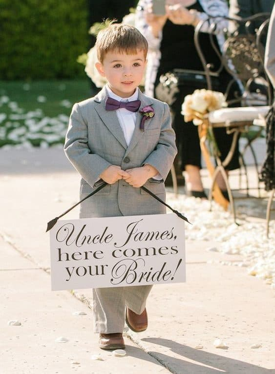 """wedding page boy holding sign """"here comes the bride"""""""