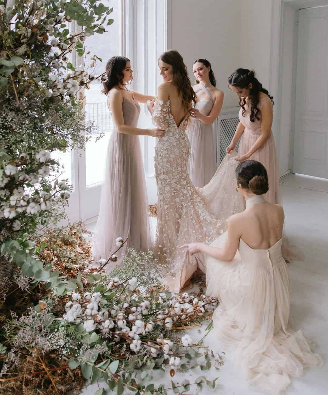 the bridesmaids help the bride with wedding dress