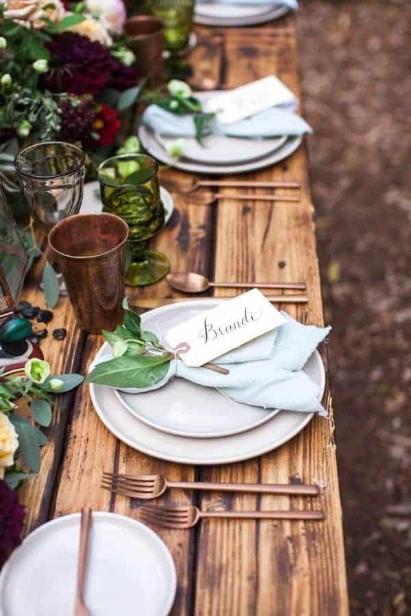 γαμήλιο τραπέζι διακοσμημένο με μπορντό λουλούδια και πράσινα φύλλα