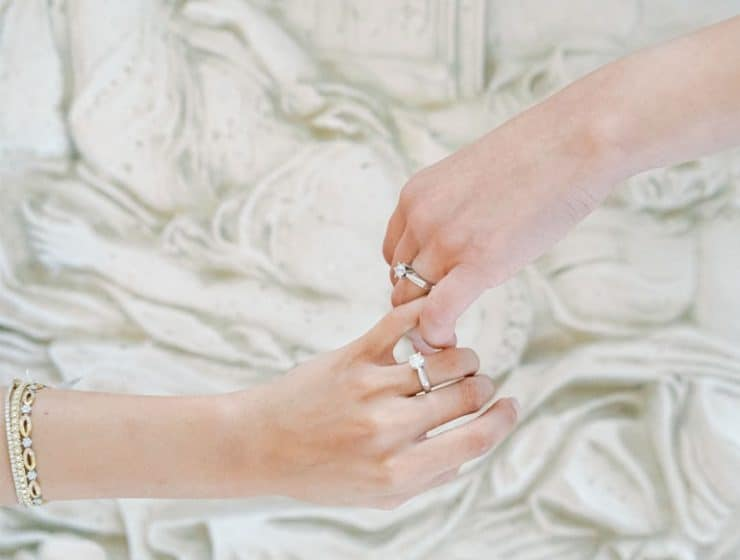 Ένα ζευγάρι κράταει χέρια, με βέρες από το κατάστημα Yiotis Jewellery.